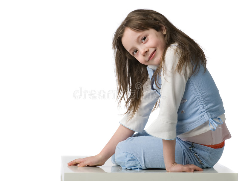 Little beautiful girl portrait. Little beautiful girl in blue clothes sits on a white chair, isolated on white royalty free stock photography