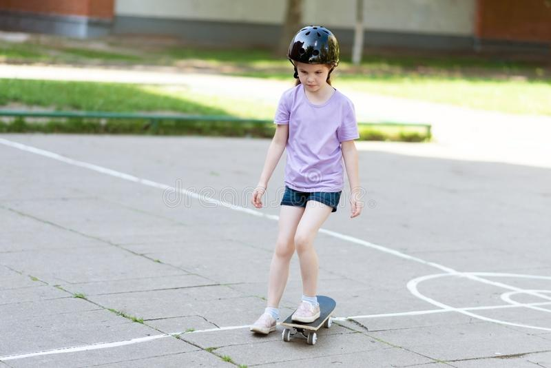 Little beautiful girl rides a skateboard. For any purpose stock photo