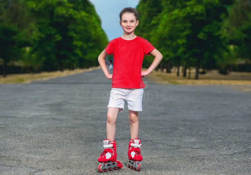 Little beautiful girl roller-skating in the summer royalty free stock photography