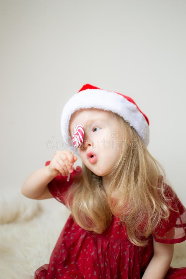Little Beautiful Girl in Santa Hat Red Party Dress Waiting for Christmas and New Year royalty free stock photos