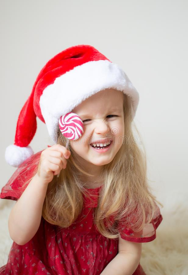 Little Beautiful Girl in Santa Hat Red Party Dress Waiting for Christmas and New Year stock images