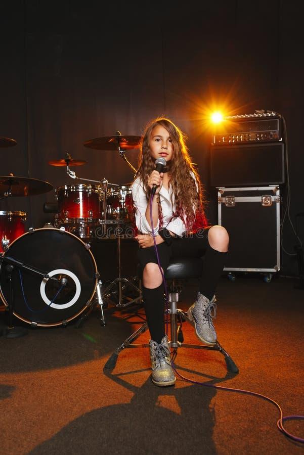 Beautiful girl singing in recording studio royalty free stock photography