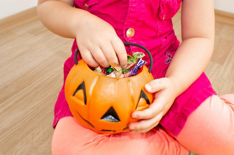 Little beautiful girl sitting with a pumpkin with candies in her hands, on Halloween. royalty free stock photos