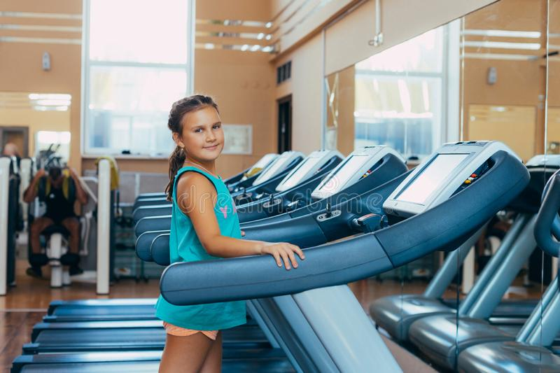 Beautiful girl with a smile runs on a trainer in the gym. Little beautiful girl with a smile runs on a trainer in the gym stock photos