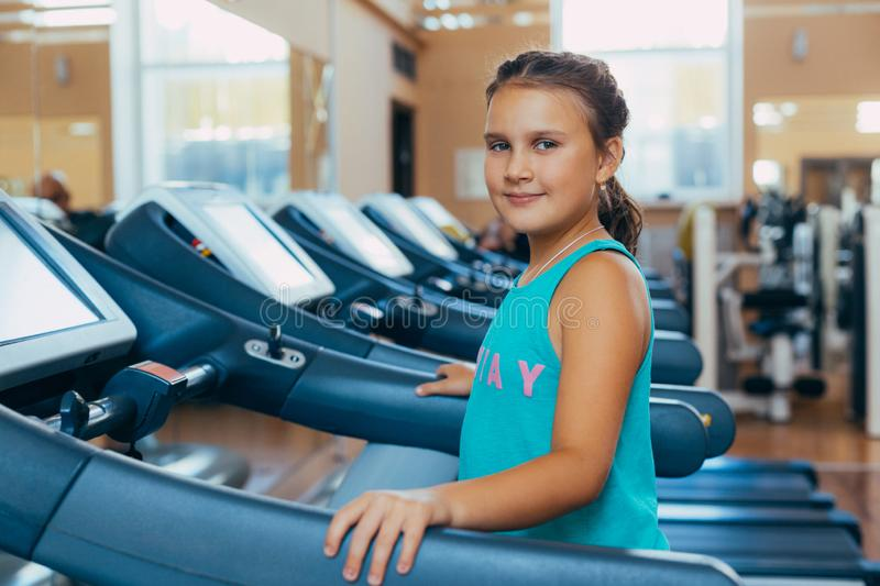 Beautiful girl with a smile runs on a trainer in the gym. Little beautiful girl with a smile runs on a trainer in the gym royalty free stock photography