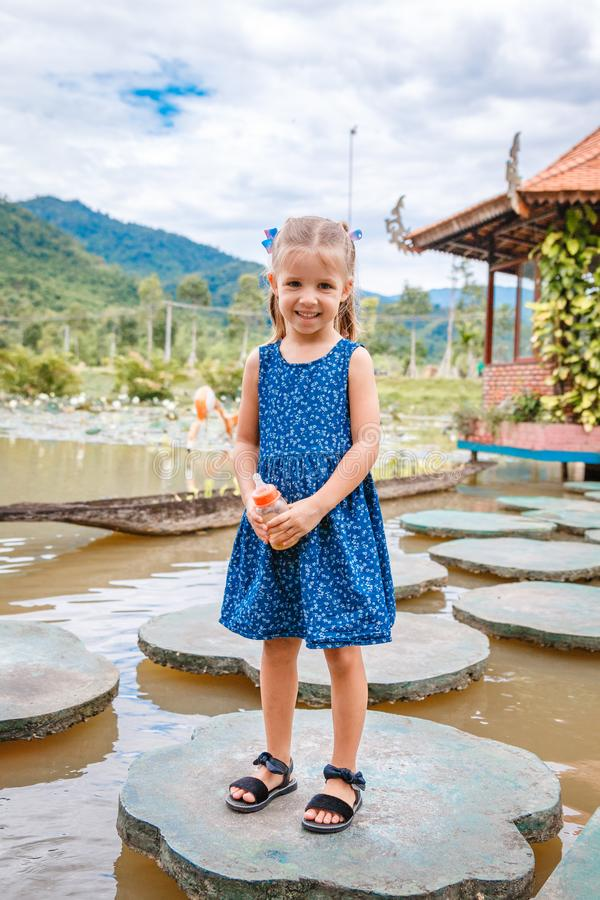 Little beautiful girl standing with a bottle of fish food in hand. Yang Bay Vietnam stock photo