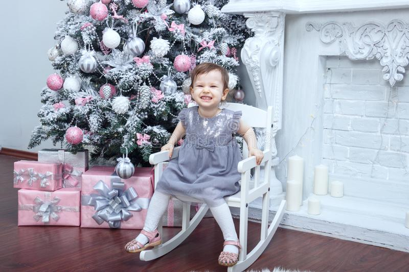 A little beautiful girl two years old dressed in a gray dress with a pink bow is sitting in a chair near an elegant New Year tree royalty free stock images