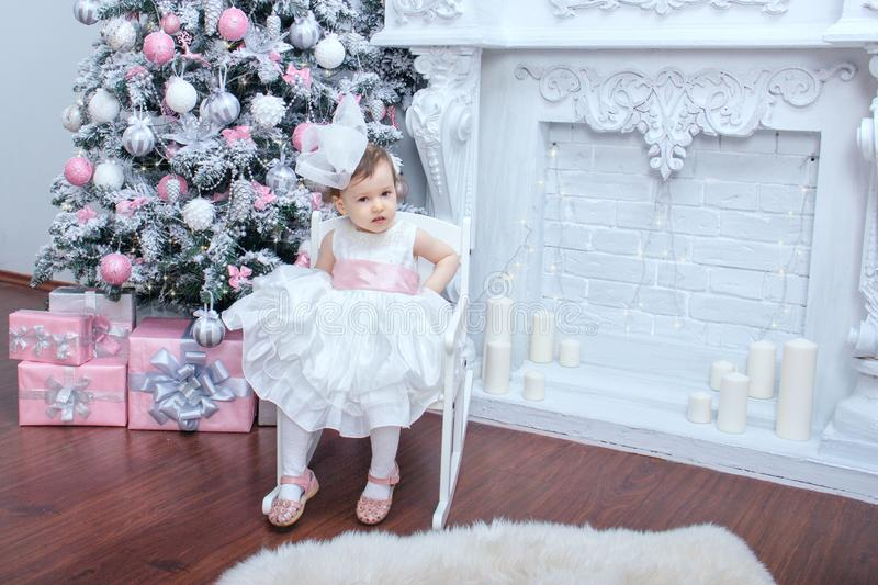 A little beautiful girl two years old dressed in a magnificent white dress with a pink bow is sitting in a chair near an elegant stock photo