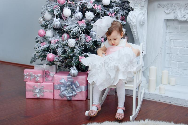 A little beautiful girl two years old dressed in a magnificent white dress with a pink bow is sitting in a chair near an elegant N royalty free stock photo