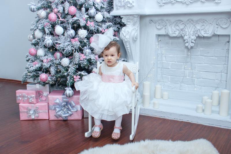 A little beautiful girl two years old dressed in a magnificent white dress with a pink bow is sitting in a chair near an elegant stock photos