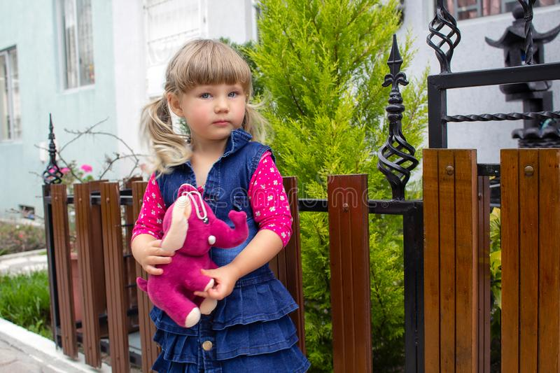 Little beautiful girl walks with a soft toy in their hands. On open air. stock photos