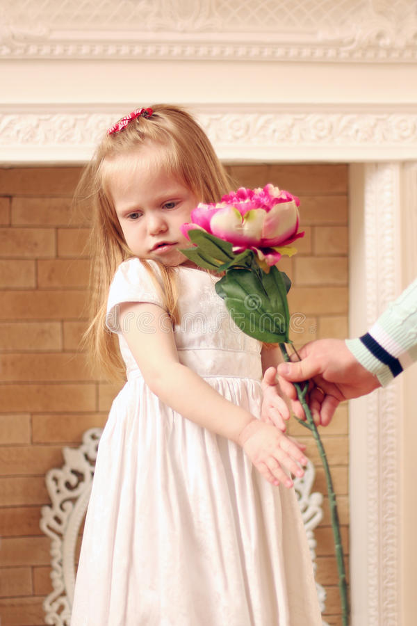 Little beautiful girl in white dress and male hands royalty free stock images