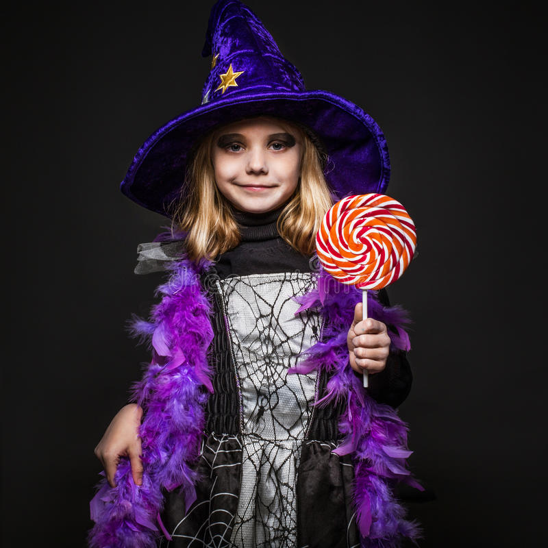 Little beautiful halloween witch with colorful candy stock image