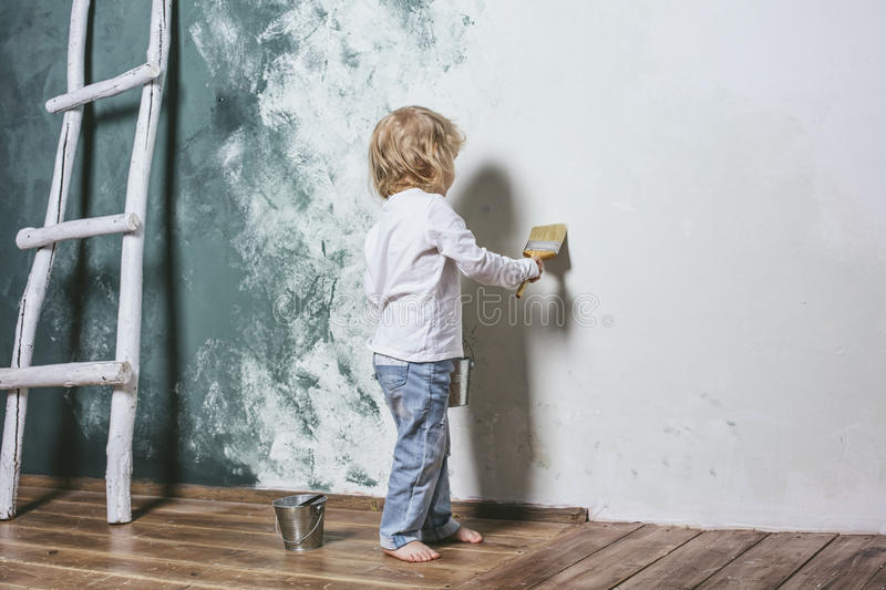 Little beautiful and happy child in jeans paint the wall with br. Little beautiful and happy child in jeans and barefoot paint the wall with brush at home stock photos
