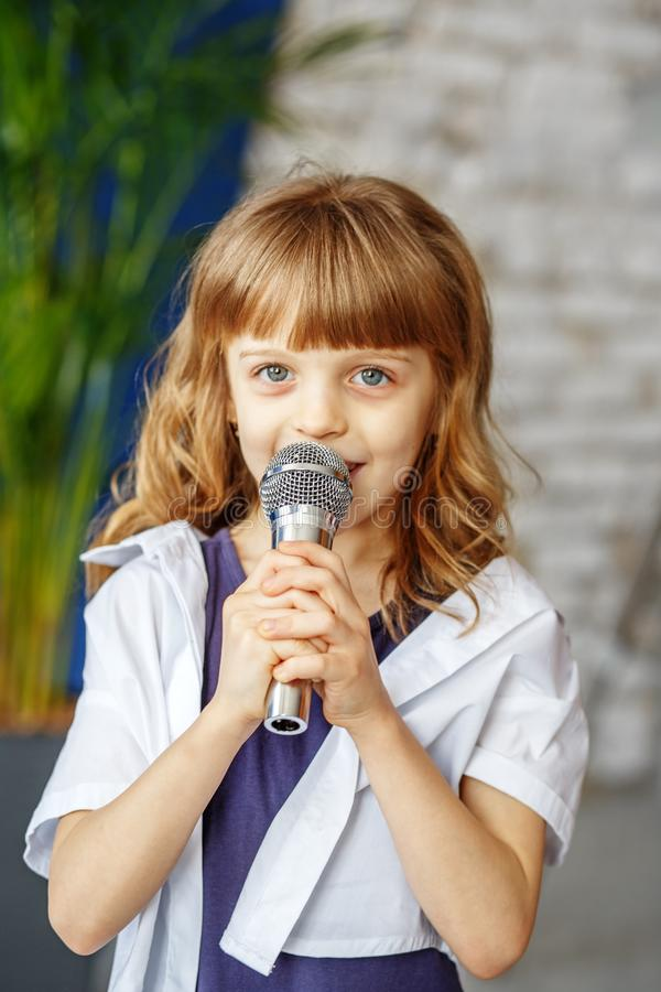A little beautiful kid sings a song in a microphone. The concept stock images