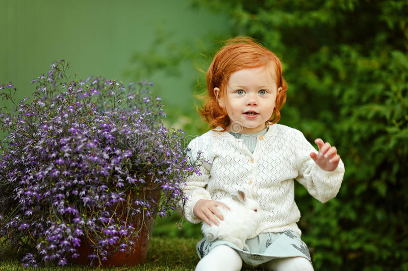 Little beautiful red-haired girl baby girl smiling and holding a royalty free stock photo
