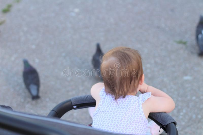 Little, beautiful, smiling, cute redhead baby in a pram out-of-doors in a sleeveless shirt and looking forward. Faceless, impersonal, featureless, child stock photography