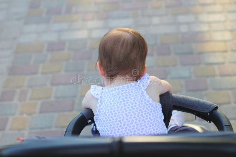 Little, beautiful, smiling, cute redhead baby in a sleeveless shirt in a pram out-of-doors drops hands down and looking forward. Faceless, impersonal royalty free stock images