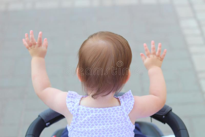 Little, beautiful, smiling, cute redhead baby in a sleeveless shirt in a pram out-of-doors raises his hands up looking forward. Faceless, impersonal stock photography