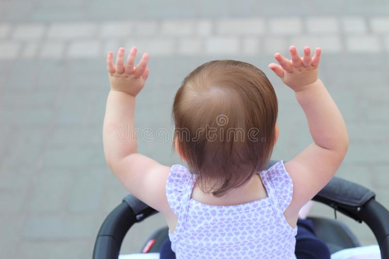 Little, beautiful, smiling, cute redhead baby in a sleeveless shirt in a pram out-of-doors raises his hands up looking forward. Faceless, impersonal stock images