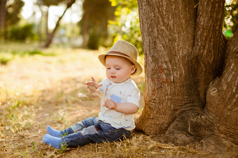 Little big-eyed little boy in a hat sits near the tree at sunset stock images