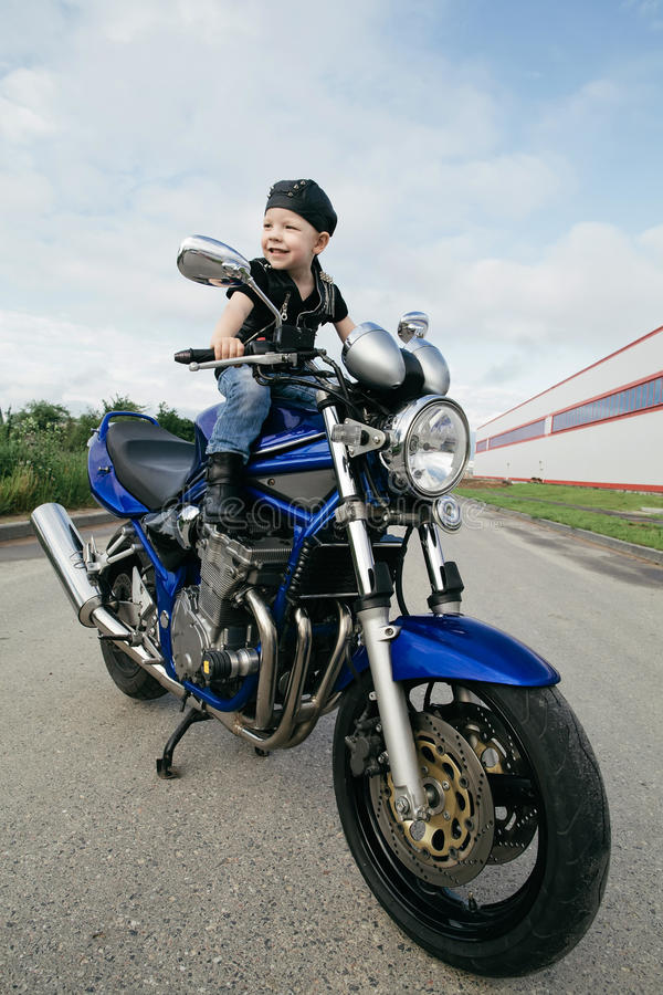 Little biker on road with motorcycle. Cute little biker on road with motorcycle stock photography