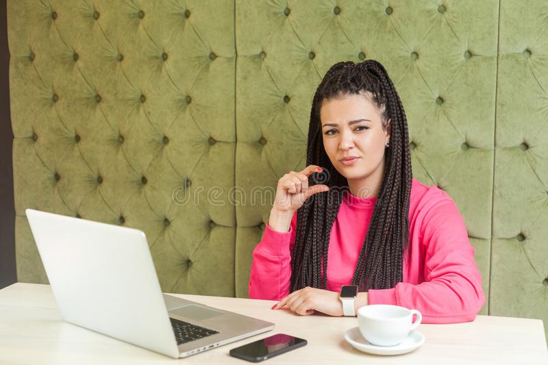 Little bit! Portrait of attractive young girl with black dreadlocks hairstyle in pink blouse are sitting in cafe, working and royalty free stock photos