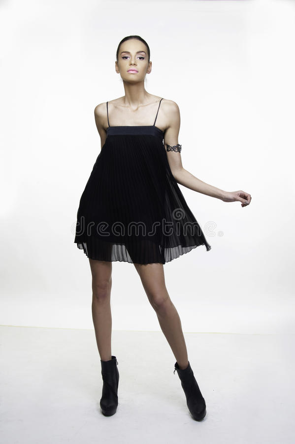 Little black dress fashion model posing. Beautiful girl fashion model posing in little black dress isolated on white royalty free stock photos