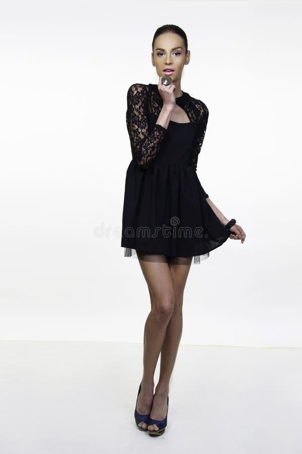 Little black dress fashion model posing. Beautiful girl fashion model posing in little black dress isolated on white stock photography