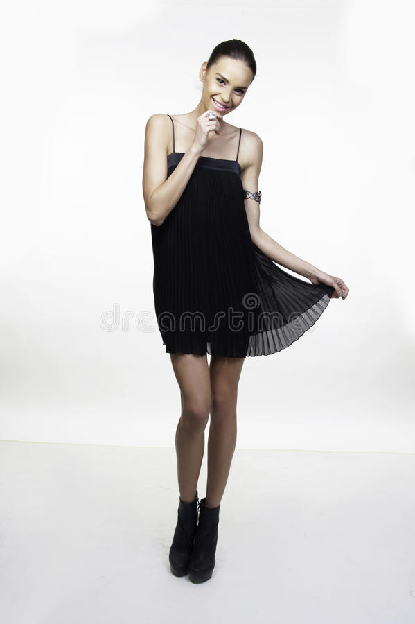 Little black dress fashion model posing. Beautiful girl fashion model posing in little black dress isolated on white stock image