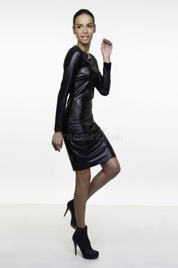 Little black dress fashion model posing. Beautiful girl fashion model posing in little black dress isolated on white royalty free stock photo
