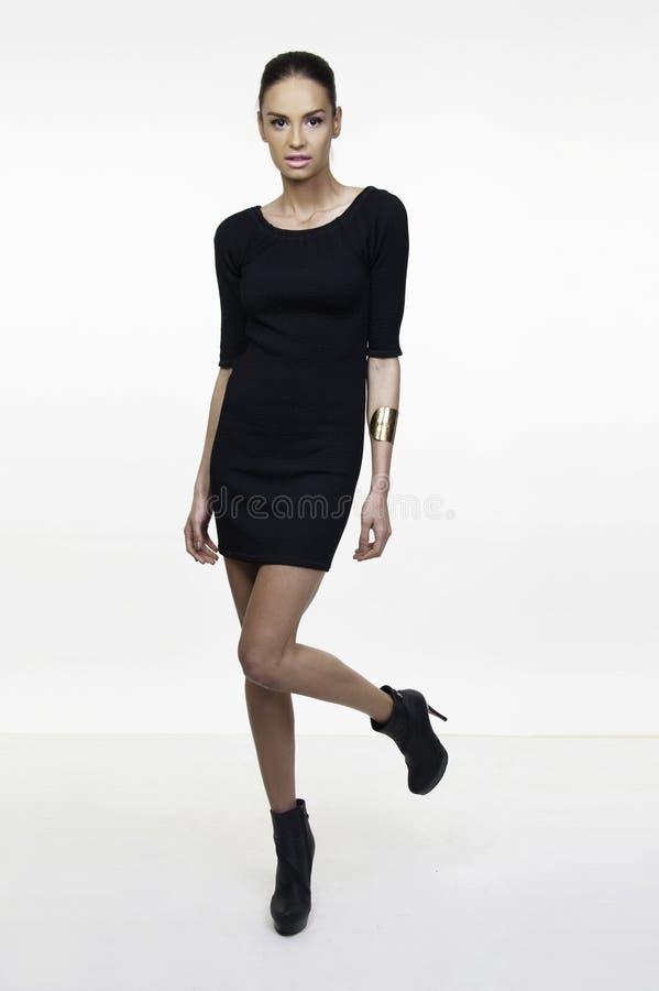 Little black dress fashion model posing. Beautiful girl fashion model posing in little black dress isolated on white stock photo