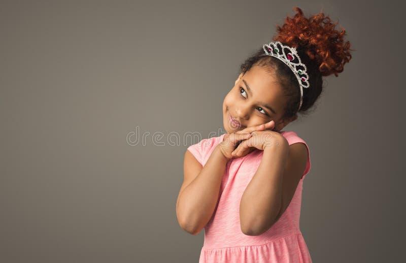 Little black girl dreaming, wearing tiara. Dreamy little princess. Cute black girl in tiara at gray studio backdrop, copy space stock photos