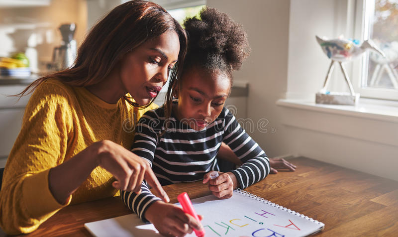 Little black girl learning to read. Learning the alphabet royalty free stock photography
