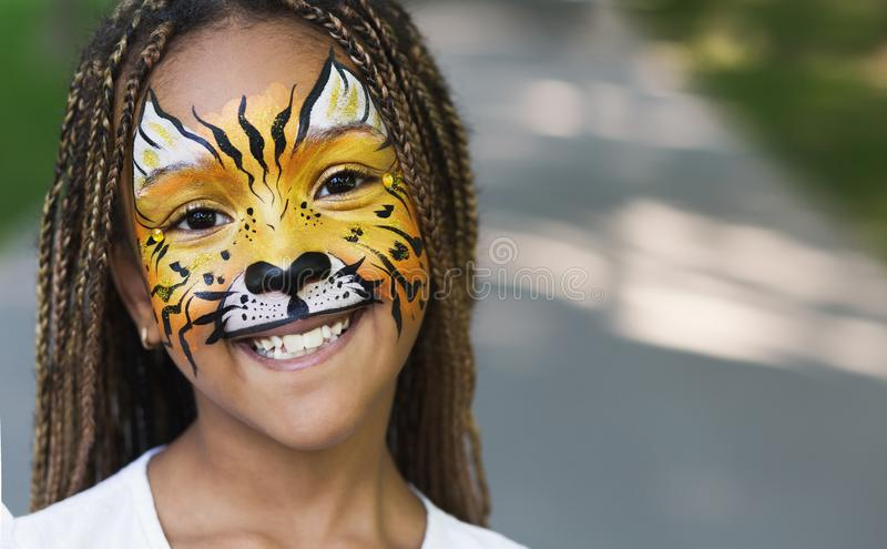 Little black girl with tiger face painting. Adorable little african american girl with tiger face painting, smiling at camera outdoors, copy space stock photo