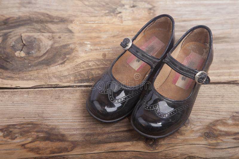 Little black shoes on wooden background royalty free stock photos