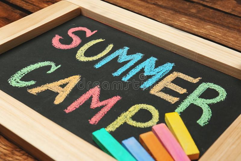 Little blackboard with text SUMMER CAMP chalked royalty free stock photo