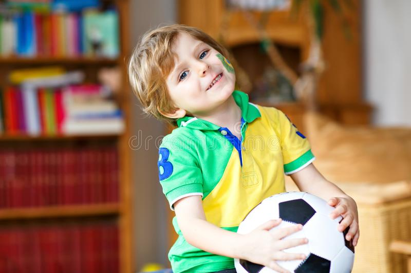 Little blond adorable kid boy with ball watching soccer football cup game on tv. Funny happy crying child fan having fun stock image