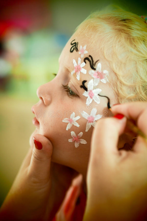 Little blond blue eyed girl face painting royalty free stock image