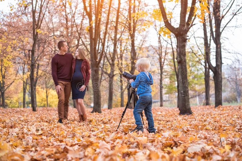 Little blond boy with a big SLR camera on a tripod. Photographs a married couple, pregnancy. Family photo session royalty free stock photo