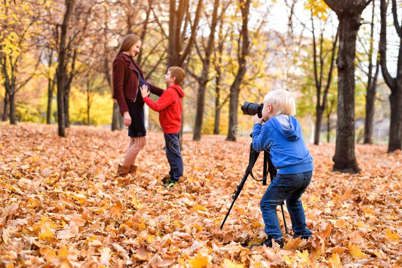 Little blond boy with a big SLR camera on a tripod. Photographs a pregnant mother and son. Family photo session stock image