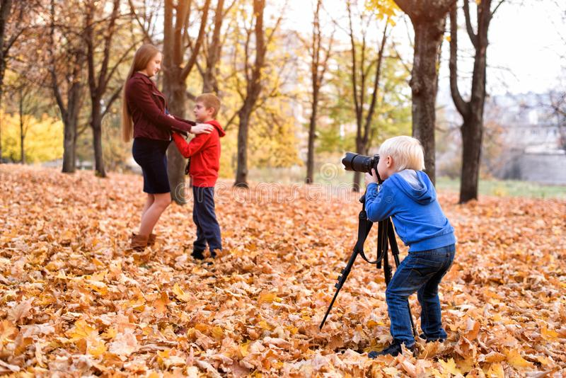 Little blond boy with a big SLR camera on a tripod. Photographs a pregnant mother and son. Family photo session stock photos