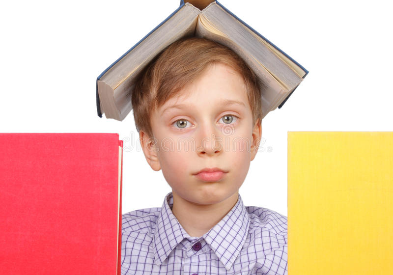Little blond boy with a book on his head looking tired from behind two colorful books isolated on white royalty free stock photo