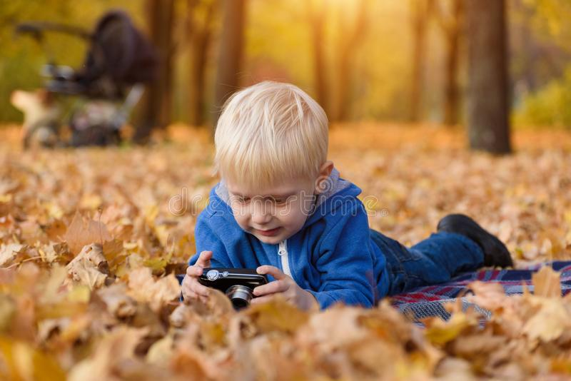 Little blond boy with camera lying on a plaid, yellow autumn leaves. Fall day royalty free stock image