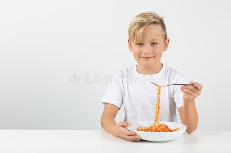 Little blond boy eats spaghetti and smiles royalty free stock photos