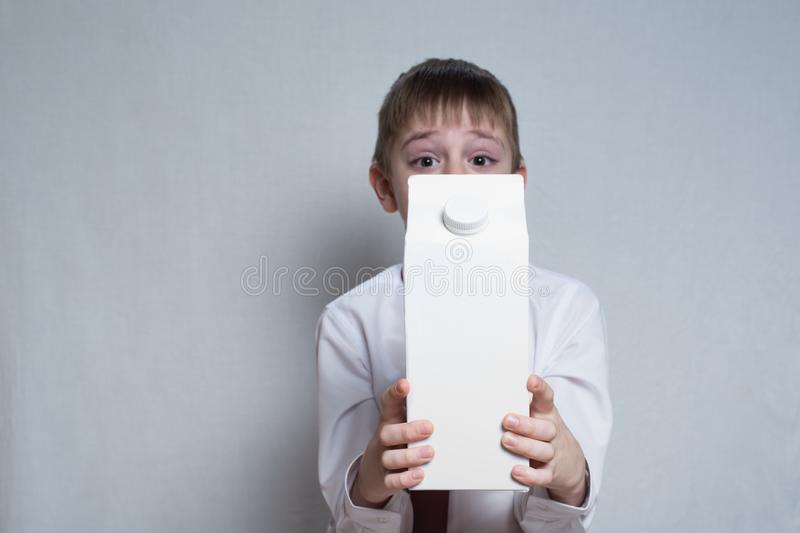 Little blond boy holds and shows a big white carton package. White shirt and red tie. Light background stock photos