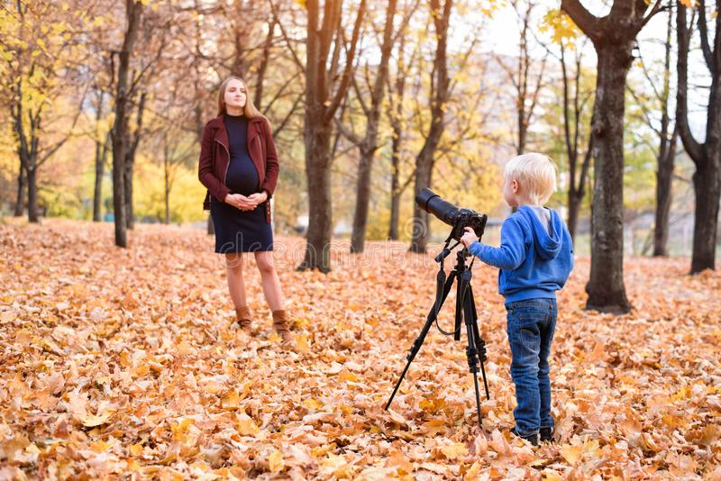 Little blond boy with a large reflex camera on a tripod. Photographs a pregnant woman. Family photo session royalty free stock photo