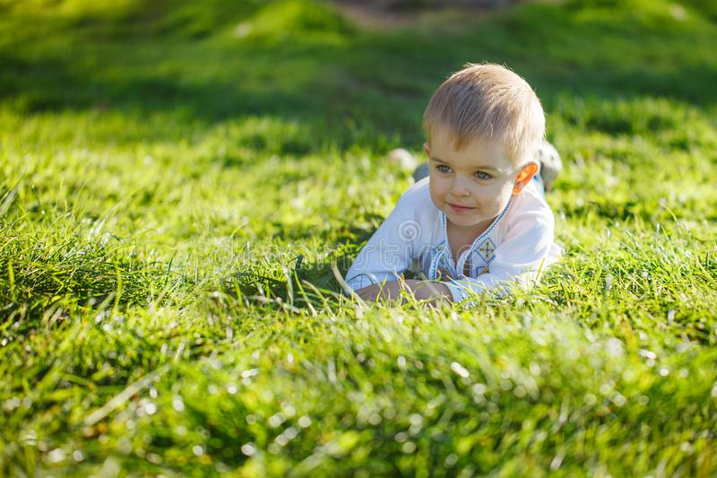 Little blond boy lying on green grass in sunny summer day. stock images