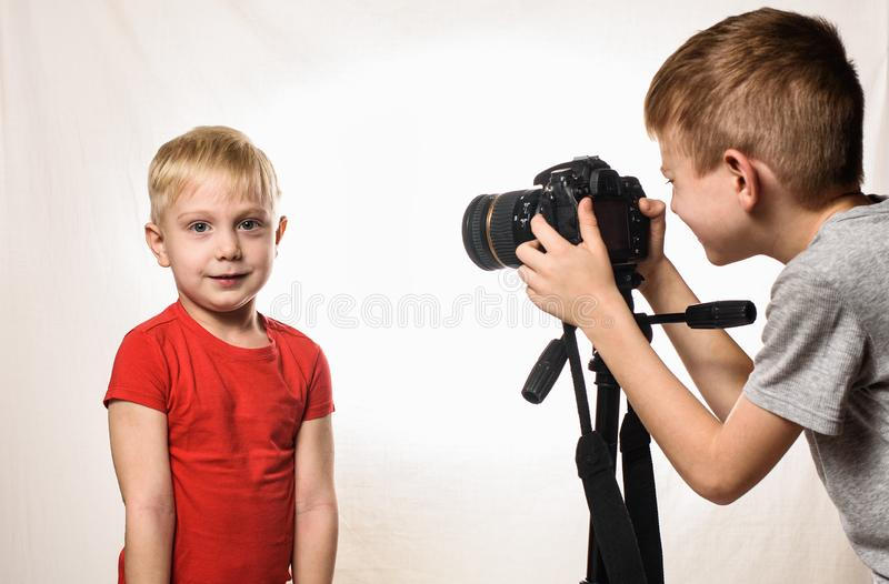 Little blond boy is ready to give the interview, boy takes it on video camera. Young video blogger. White background.  royalty free stock photography