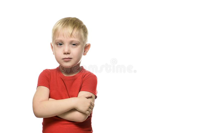Little blond boy in a red shirt stands squinting with folded arms. Isolate on white background.  stock images